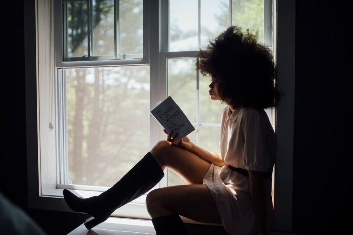 A girl reading a book by the ledge of the window