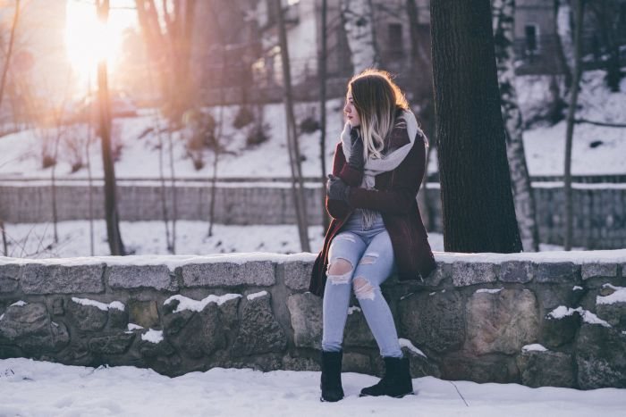 A woman sitting in the park with snow