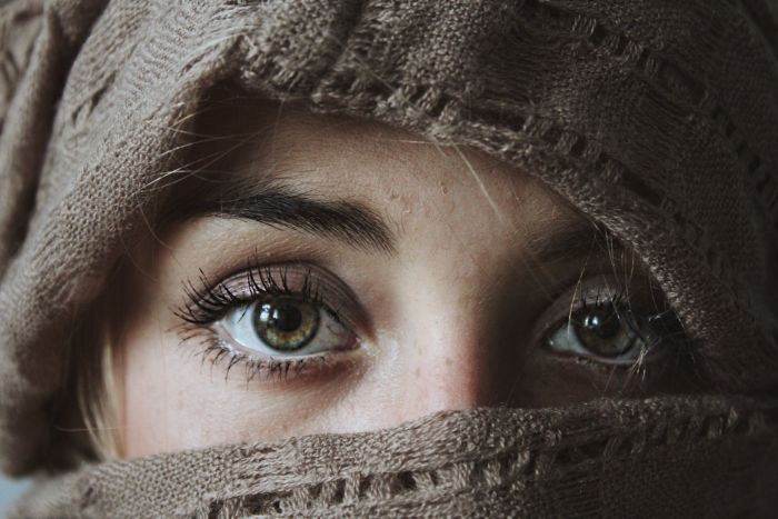A woman's eyes peering out of her hoodie