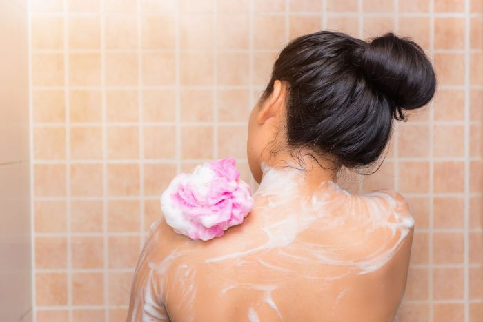 a woman taking a showr after returning home to prevent the spread of the coronavirus