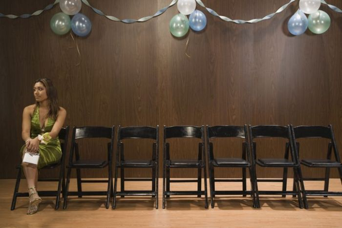 A woman alone at a party because she isn't a fun person.