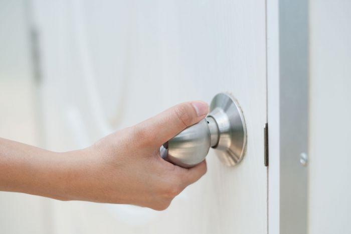 A woman touching a doorknob with dirty hands bringing infection back into her home.