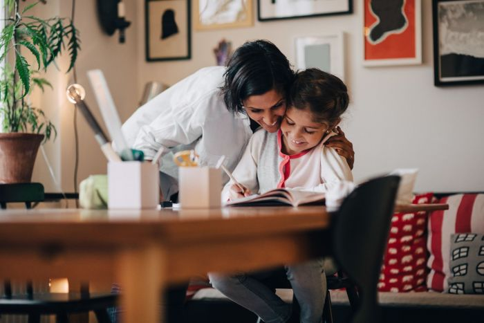A mother spending some quality time with her daughter by helping her with her homework.