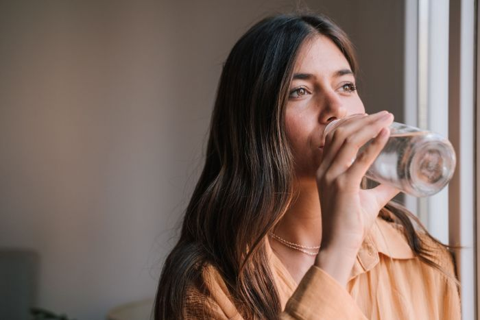 A woman drinking more water to get in more movement in a day