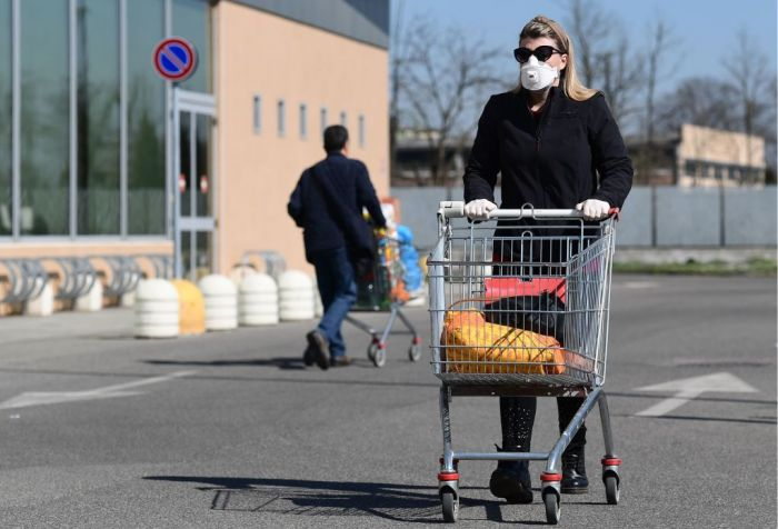 A woman parking further from the supermarket to get in some more exercise throughout the day.