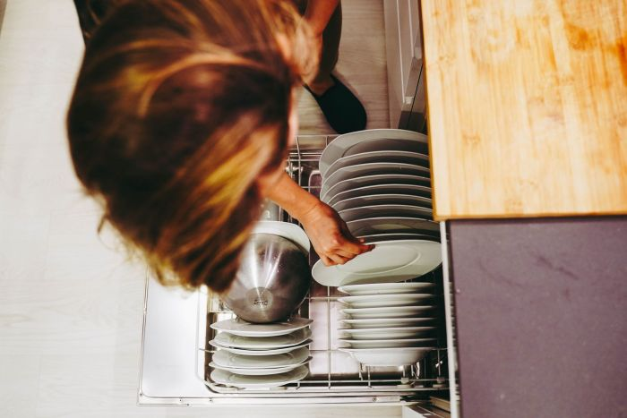 A mother unloads the dishes and does her household chores to clear time to spend with her children.