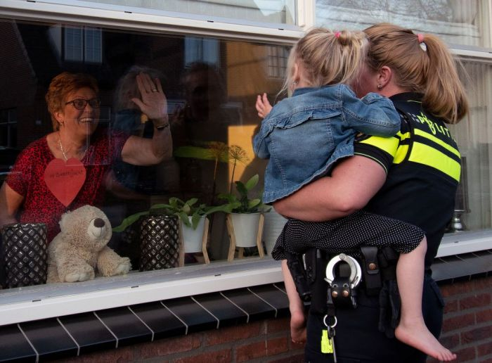Kids visit their mother on Mother's Day through the window because of social distancing.