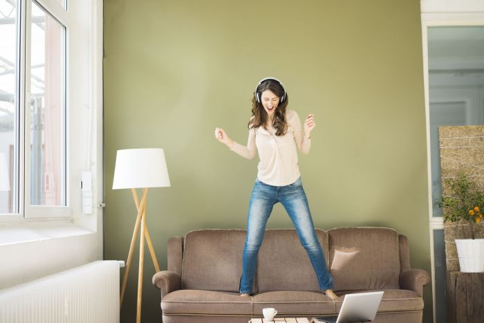 A woman dancing around her apartment to get in some exercise during her day.