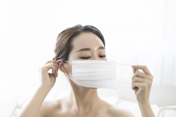 Woman making sure her mask sits right on her face.