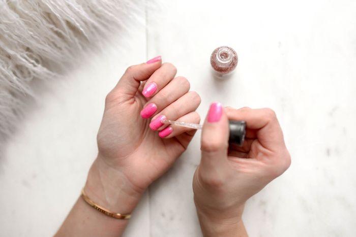 Woman applying her nail polish.